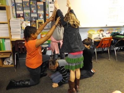 Students practice making tableaus using their bodies as a arts activity.